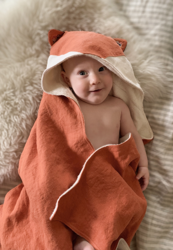 Celeste, A hooded baby towel with fox ears made in orange heavy weight linen with white appliqué on the hood...