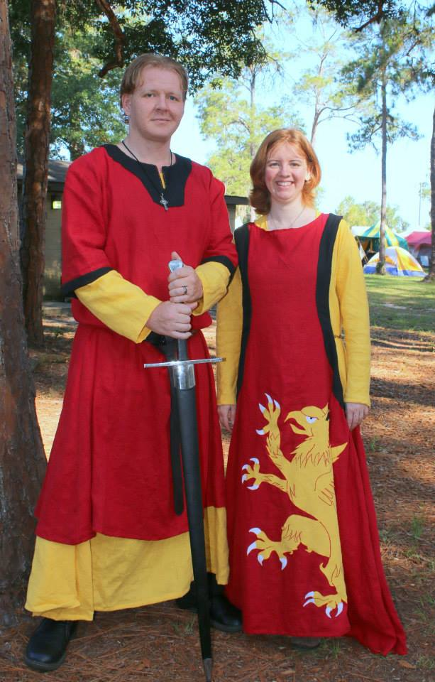 Crissy, 12th century Germanic paired tunics for him and a 13th century sideless surcoat with griffin appliqu...