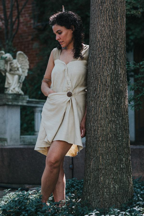 Mandi, 100% linen Roman Draped Mini Dress, featuring a folded asymmetrical front seam and hidden triangle p...