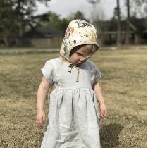 Dove mid weight linen for the dress with lace trim and  button closure.  Bonnet is reversible wi...
