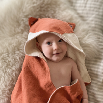 A hooded baby towel with fox ears made in orange heavy weight linen with white appliqué on the h...