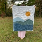 Hand quilted baby quilt with a Mountain View.