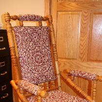 Antique recovered glider chair with decorative nail heads