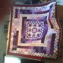 It is a queen size quilt I made in purples and burgundy's and I donated it to a group to be raff...
