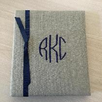 Oatmeal linen baby book with red monogram and grosgrain ribbon sold online at; https;//www.wayco...