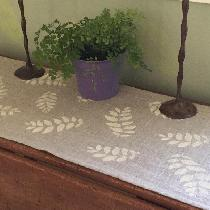 Table runner in Natural Rustic linen with off white handprinted leaf pattern.