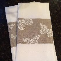 Linen tea towels with hand-stamped butterflies and decorative stitching.