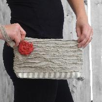 A strapped clutch made from two medium weight linens and adorned with a linen rosette. The upper...