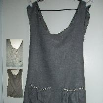 A gray linen criss-cross tunic apron, trimmed with contrasting gray and white bias tape and two...