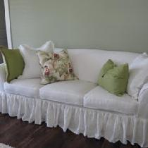 Ruffled bleached white washed linen sofa slipcover with ruffled skirt and self cording detail....