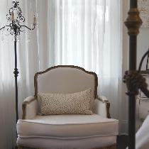Vintage Chair recovered in white linen fabric  for bedroom with white linen bedding.